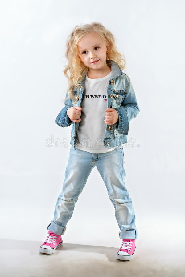 Little fashionista posing in denim suit stock images