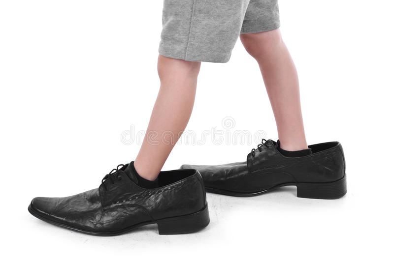 Little feet in big shoes. Boy`s little feet in big black style shoes stock images