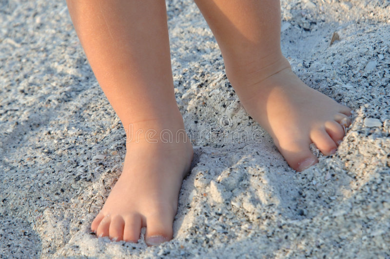 Little feet in the sand. Little toddler girl bare feet in the sand stock image