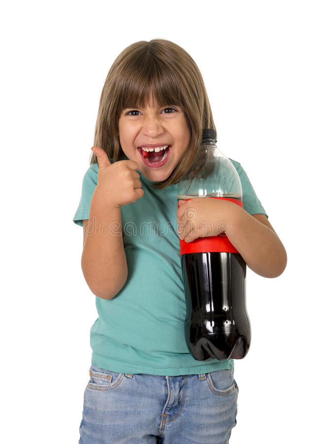 Little female child giving thumb up holding big cola soda bottle smiling happy in children sugar addiction and bad habit nutrition. Concept isolated on white royalty free stock image