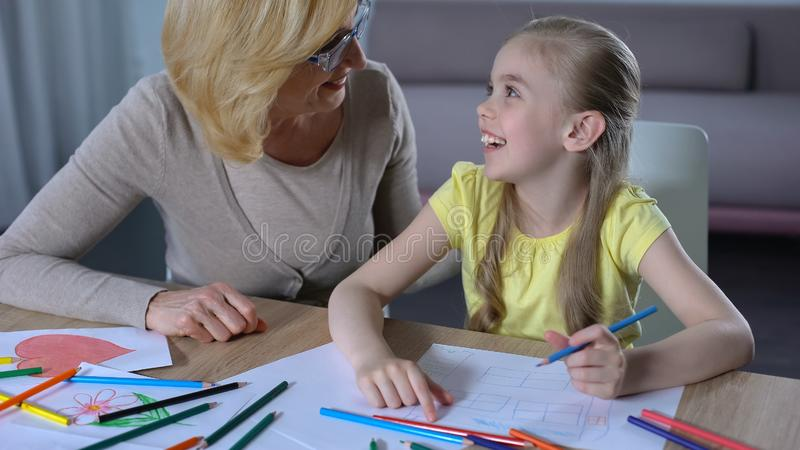 Little female child painting with colours pencils, leisure time with granny stock photography