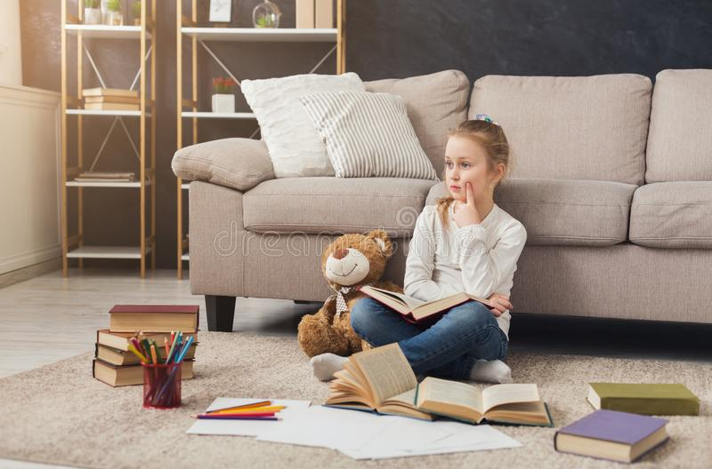 Little female child reading book while sitting on the carpet royalty free stock images