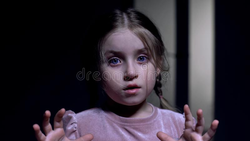 Little female child scared, looking at camera, afraid of darkness, ghosts phobia royalty free stock photo
