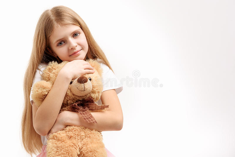 Little female kid keeping toy. Small girl is hugging soft toylike bear and looking at camera with smile. Portrait. Isolated. Copy space on right side royalty free stock photo