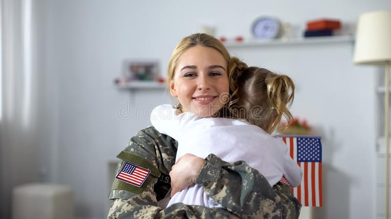 Little female kid with US flag embracing soldier mother, family reunion, patriot stock images