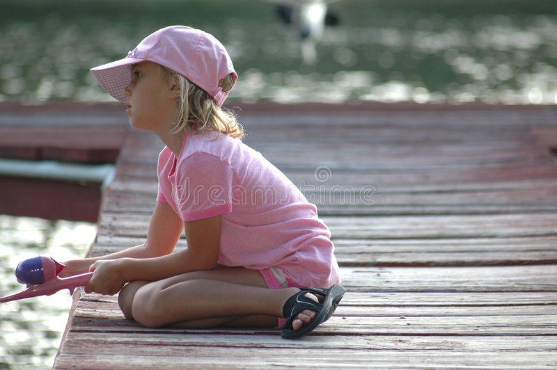 Little Fishing girl. Learning how to firsh, copy text space to the right of girl. Little girl sits on boat dock and waits for that catch stock photos