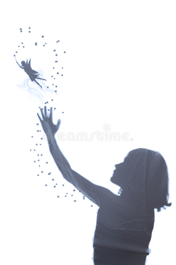 Little Flying Fairy Girl. The silhouette of a little girl and a fairy. The girl stretches out his hand to reach the fairy flying that, with the magic wand in stock photos