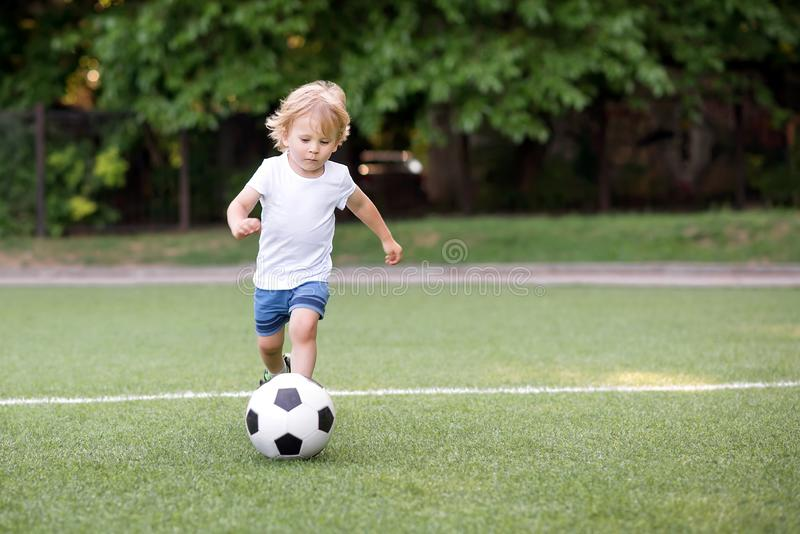 Little football player: blonde child in white shirt and blue shorts running along the green soccer field ready to kick ball. stock photography