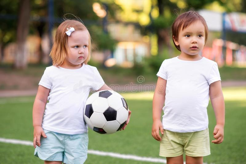 Little football team: toddler girl with soccer ball and boy in sports uniform standing at football field together stock image