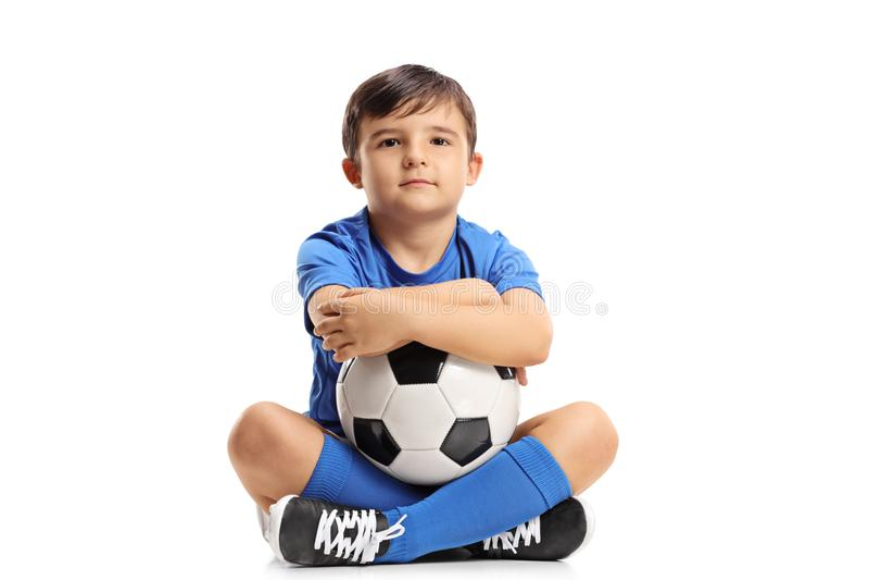 Little footballer sitting on the floor royalty free stock photography