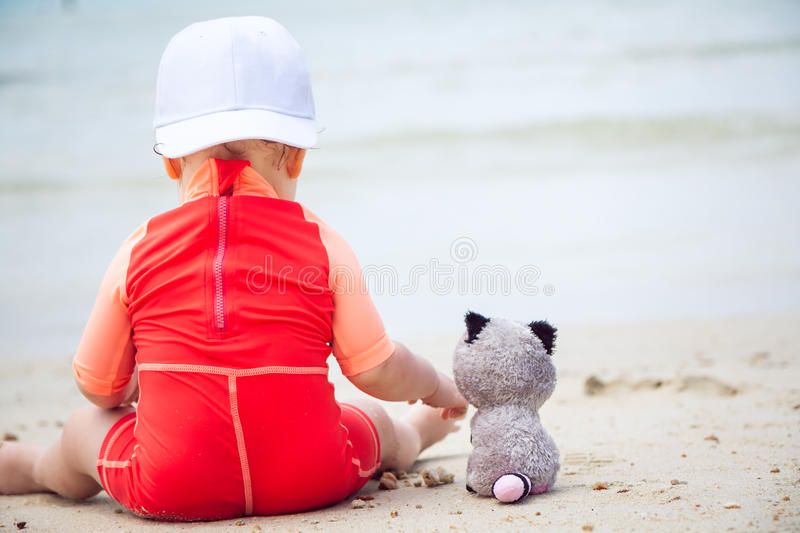 Little Friends. Baby playing with toy animal on beach with sea on background and copy space stock photo