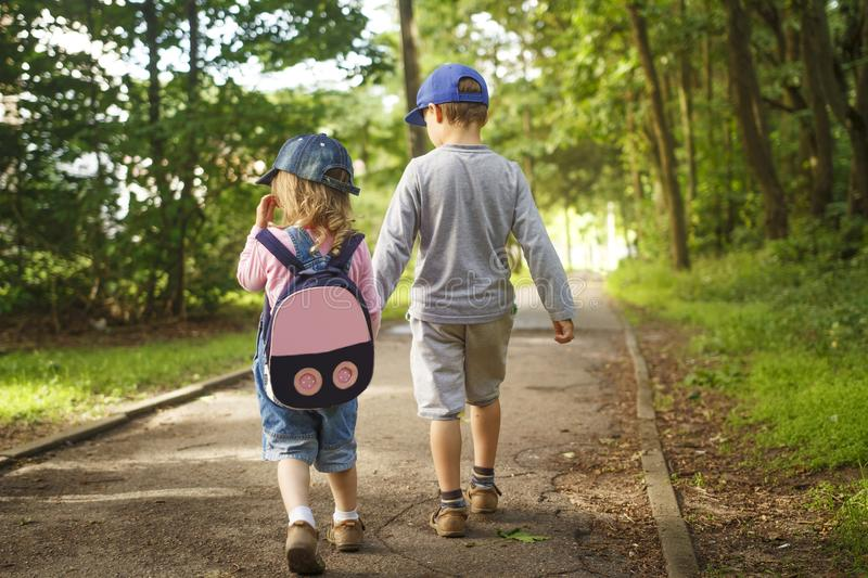 Little friends children hold hands and walk along path in park on summer day. boy and girl are walking in park outdoors royalty free stock images