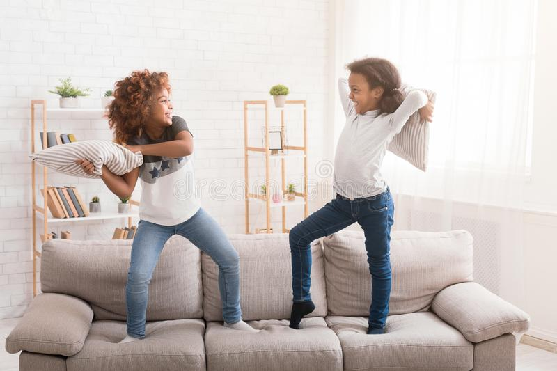 Little friends fighting with pillows, having fun together royalty free stock image