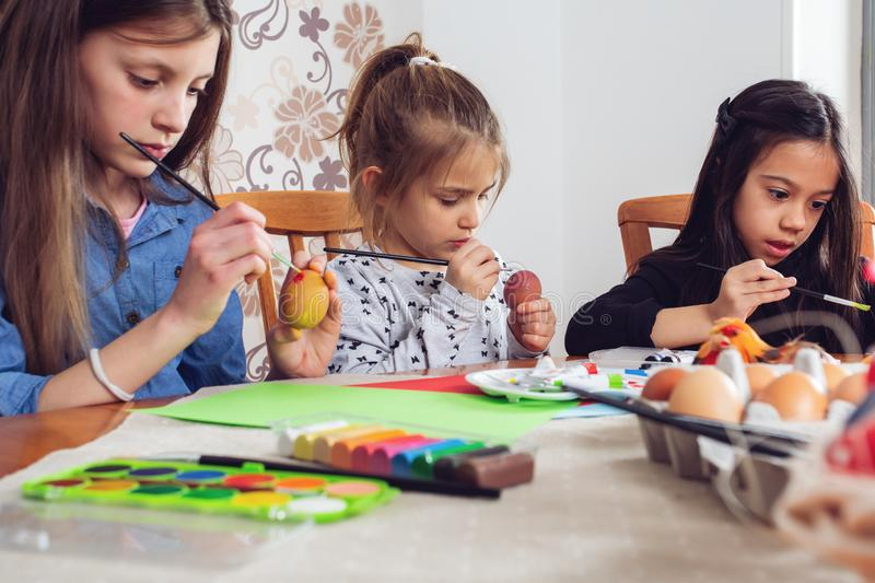 Little friends painting Easter eggs before holiday. Photo of Little friends painting Easter eggs before holiday stock photography
