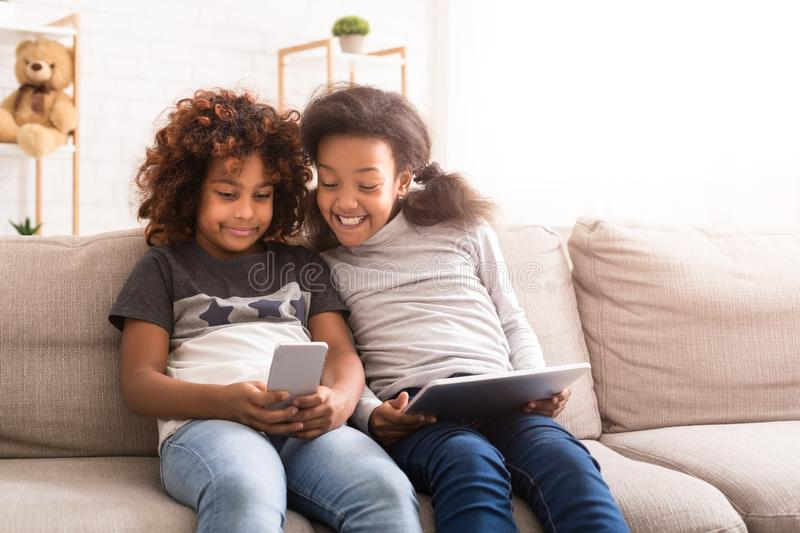 Little friends using gadgets, playing games on sofa royalty free stock images