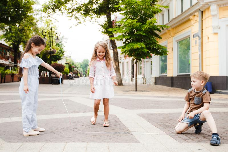 Little friends are walking around the city. Play and have fun. Three jump over the rope. royalty free stock photo