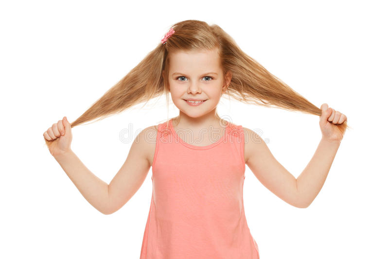 Little fun joyful girl in a pink shirt holds hands hair, isolated on white background.  stock image