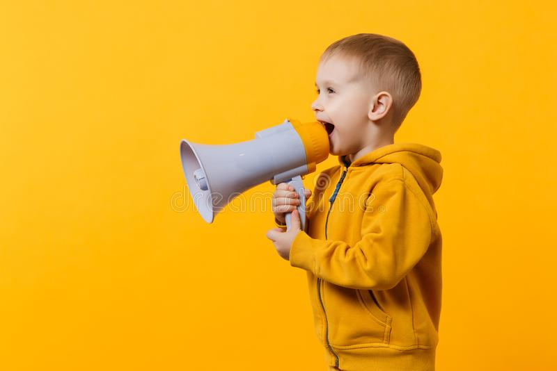 Little fun kid boy 3-4 years old in yellow clothes holding, speaking in electronic megaphone isolated on orange wall. Background, children studio portrait stock photos