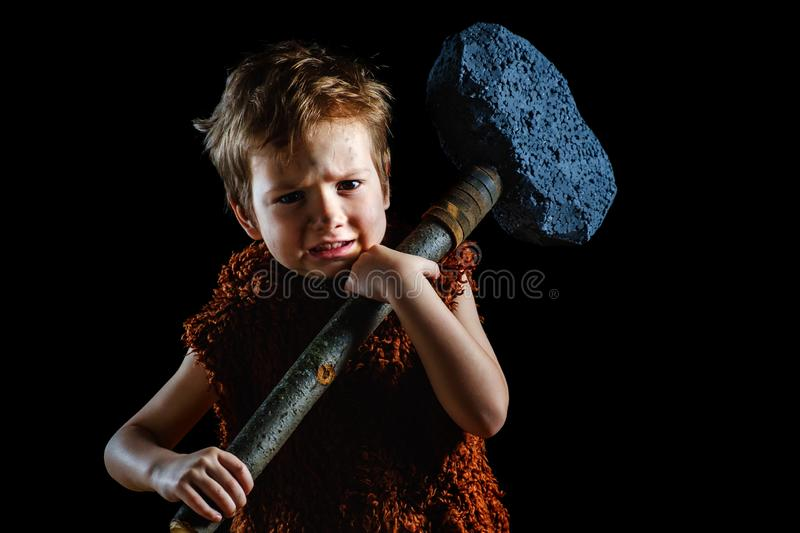 Little funny angry warrior boy. Neanderthal or a Cro-Magnon. Ancient caveman,   ancient royalty free stock photography
