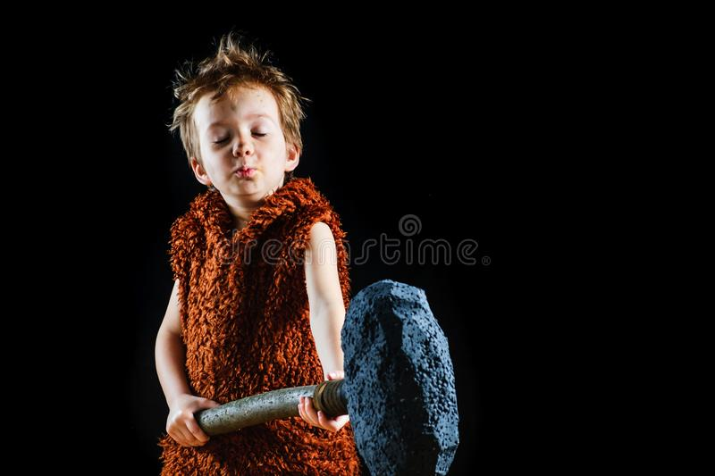 Little funny angry warrior boy. Neanderthal or a Cro-Magnon. Ancient caveman,   male savage royalty free stock images