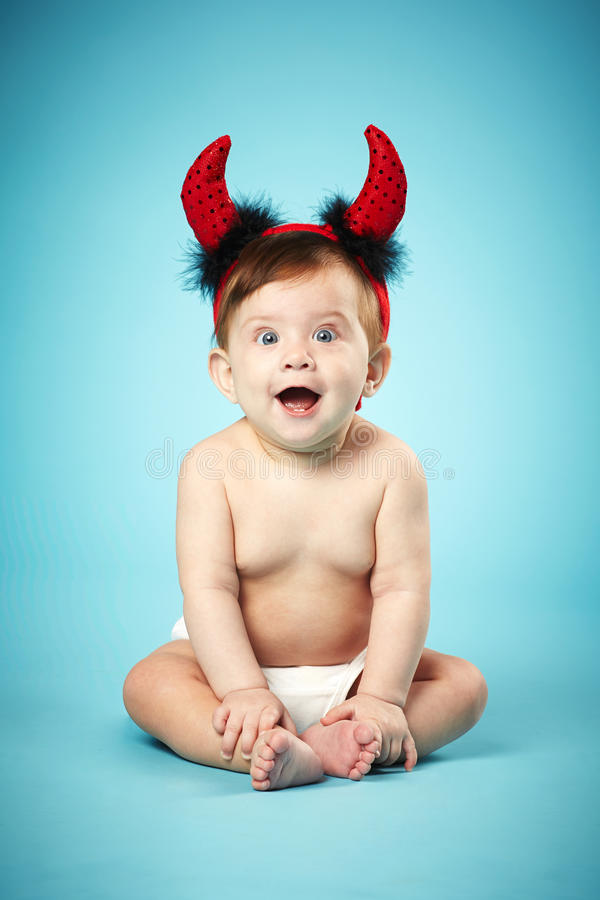 Little funny baby with devil horns stock photos