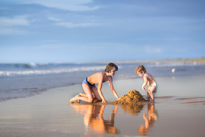 Little funny baby girl and her brother on beach. Little funny baby girl and her brother playing together on a beach royalty free stock images