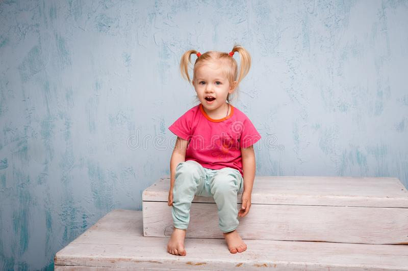 Little funny blue-eyed girl child blonde with a haircut two ponytails on her head sitting on a gossip on the background of an old. Textured wall in blue stock photo
