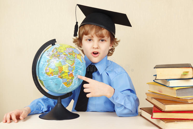 Little funny boy in academic hat showing on the globe among old books royalty free stock photo