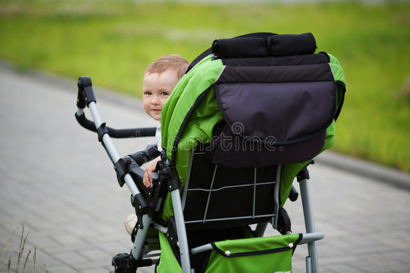 Little funny boy with baby carriage stock image