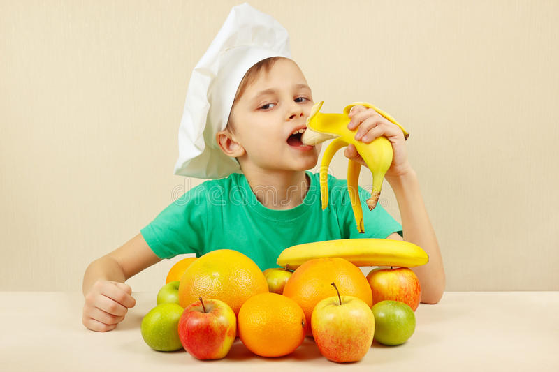 Little funny boy eat fresh banana at table with fruits royalty free stock photos