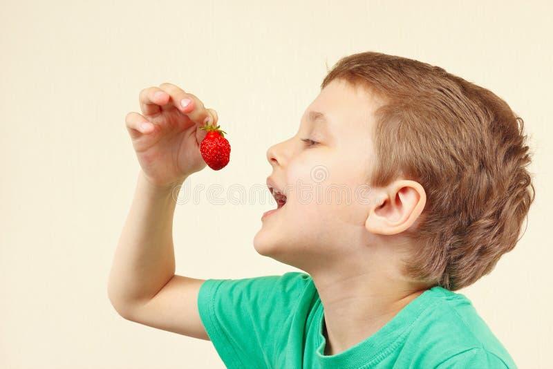 Little funny boy eating fresh sweet strawberry royalty free stock photo