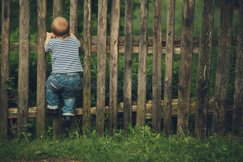 Little funny boy with fence. Outdoors stock photography