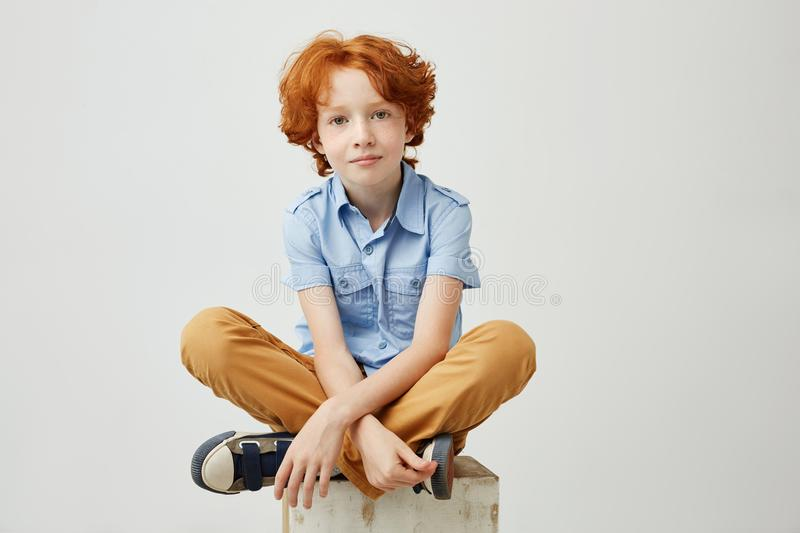 Little funny boy with orange hair and freckles sitting on wooden box in studio, looking in camera with calm and relaxed stock image