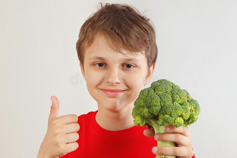Little funny boy in a red shirt recommends fresh broccoli on white background royalty free stock image