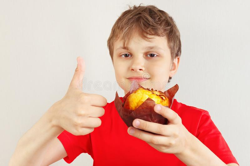 Little funny boy in a red shirt recommends muffin on white background royalty free stock photos