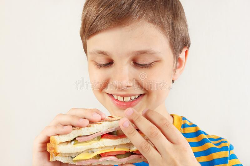 Little funny boy in a striped shirt with a double sandwich on white background stock image