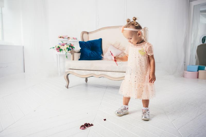 Little funny caucasian child girl dropped on the floor sweetness dessert cake and mess. Kindergarten and birthday party spoiled, royalty free stock photo