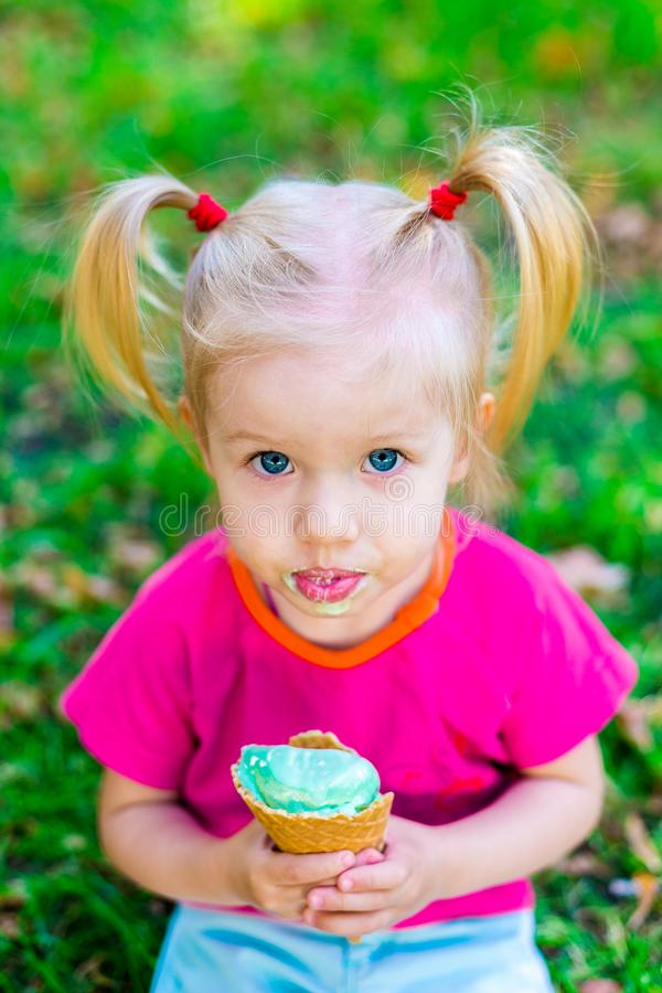 Little funny Caucasian girl blonde with blue eyes with two tails on her head eating an ice cream in a waffle cup of blue sitting o royalty free stock photos