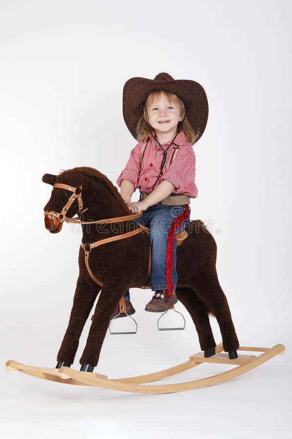 Little funny cowgirl riding horse. On white stock photography