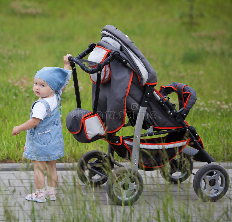 Little funny girl with baby carriage royalty free stock photos