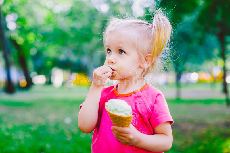 Little funny girl blonde eating sweet blue ice cream in a waffle cup on a green summer background in the park. smeared her face an stock photography