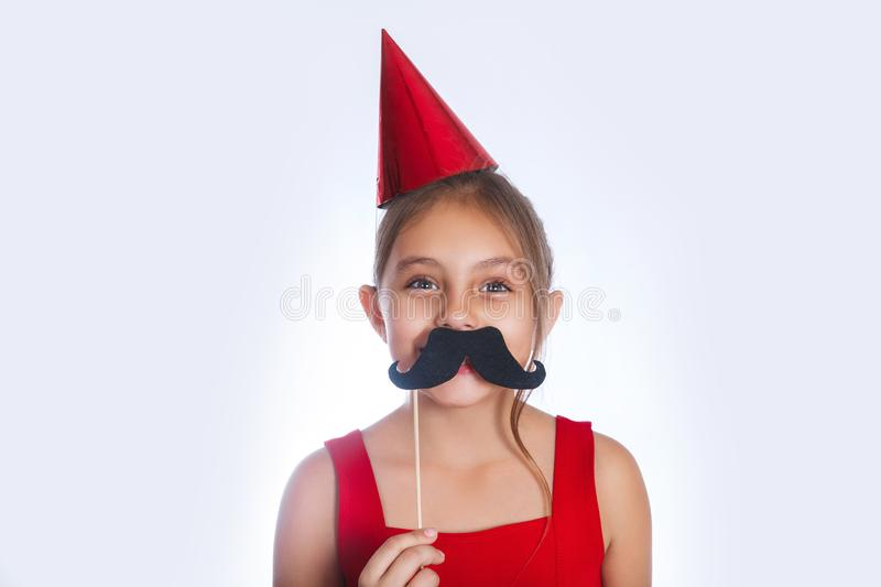 Little cute girl holding paper party sticks and having fun. Little funny girl holding paper party sticks and cap. Holidays concept stock photos