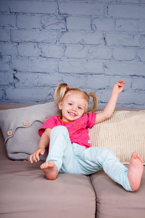 little funny girl pampering and playing on the sofa at home showing