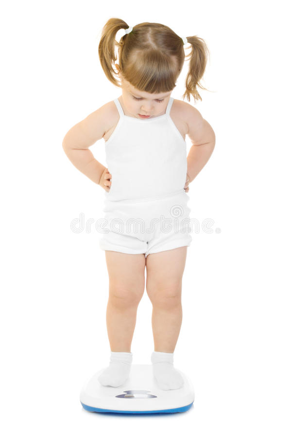 Little funny girl stand on scales royalty free stock image