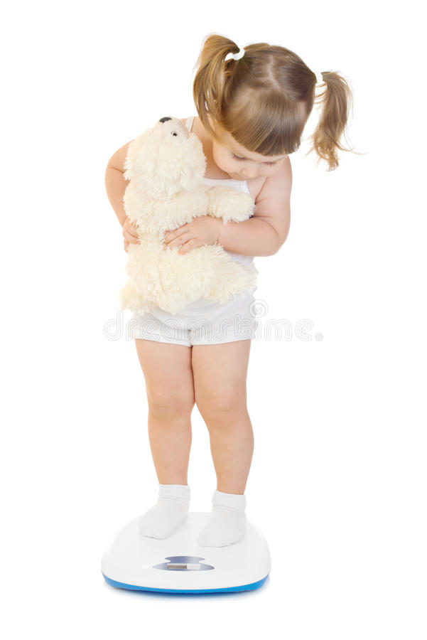 Little funny girl stand on scales stock photos
