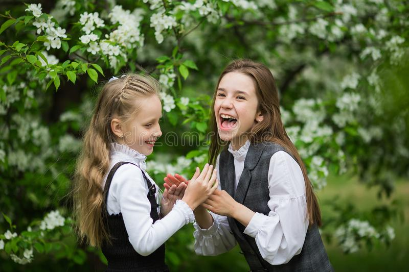 Little funny girls in stylish school uniforms play outdoors in the blossoming apple park stock photos