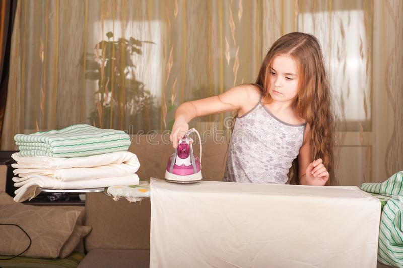 Little funny housewife with iron. Iron in the hand of the girl on the Ironing Board irons and steams clothes. Little girl playing stock photography