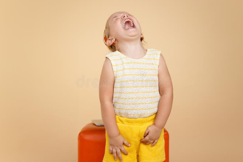 Little funny toddler girl screaming, over beige background. Horizontal view. Copy space. stock photo