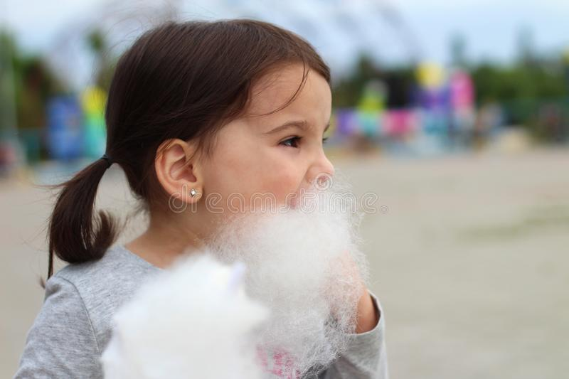 Little funny white girl with tails with narrow eyes holds cotton candy with his lips while walking outdoors stock photography