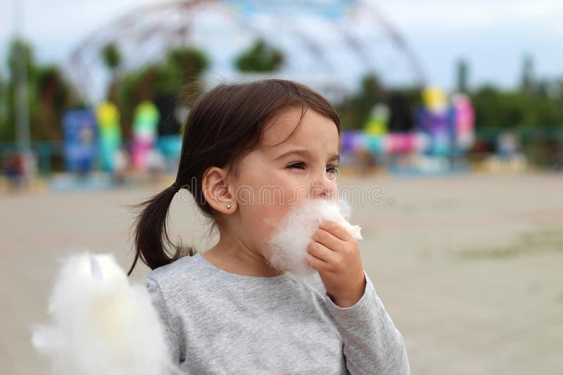 Little funny white girl with tails with narrow eyes holds cotton candy with his lips while walking outdoors royalty free stock image